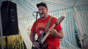 En man i röd skjorta spelar gitarr och skriker i en mikrofon