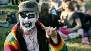 En man med corpsepaint och regnbågsjacka visar djävulshorn