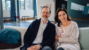 Asko Sarkola och Ira Hammermann sitter tillsammans i en soffa.
