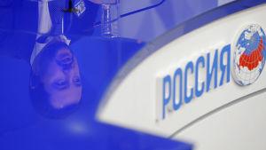 Matteo Salvinis ansikte reflekteras i ett glasbord i ryska flaggans färger.