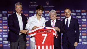 Joao Felix håller upp sin tröja tillsammans med representanter för Atletico Madrid.