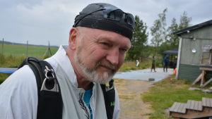 Äldre man med skägg iklädd vit jacka står utanför en grön träbyggnad.