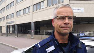 Polisen Niklas Kråknäs poserar i polisuniform framför polishuset i Böle.
