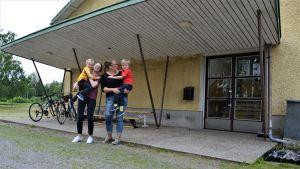 Två kvinnor med var sitt barn i famnen står utanför en gul skolbyggnad.