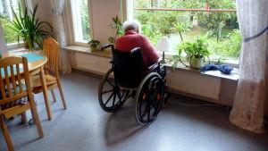 Äldre person i rullstol.
