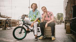 Alfons Grönqvist och Mikael Stenlund sitter i en hamn på en BMX-cykel respektive trälåda.