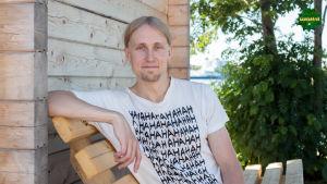 Jaakko Blomberg istuu puisella penkillä saunarakennuksen vierustalla.