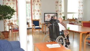 En person sitter i en rullstol på en bäddavdelning.