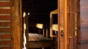 Saunan puinen ovi on raollaan. Ovesta näkyy tyhjän saunan lauteille.