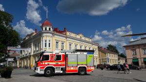 En brandbil står parkerad framför ett gult stadshus.