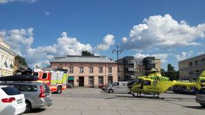 En brandbil och en räddningshelikopter står parkerade på ett torg.