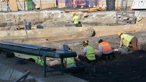 Arkeologerna som gräver i solen bredvid parkeringsbygget på Åbo Salutorg.