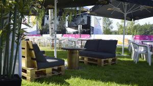 två svarta soffor byggda av lastpallar på ett festivalområde