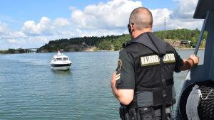 En sjöbevakare står på däck och väntar på att granska en fritidsbåt.