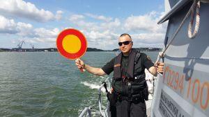 Löjtnant Mika Stormblad från Nagu sjöbevakningsstation håller upp en rödgul stoppskylt i samband med sjöbevakningens övervakning till sjöss.