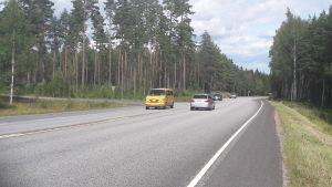 Bilar kör på en asfalterad väg. Till vänster syns ett avtag till en mindre väg.