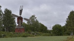 en röd vederkvarn i förgrunden och ett vindkraftverk i bakgrunden