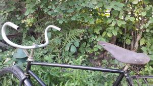 En gammal cykels styrstång, ram och sadel.