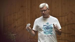 en man med glasögon pratar till en publik