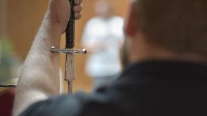 en man håller ett svär i förgrunden