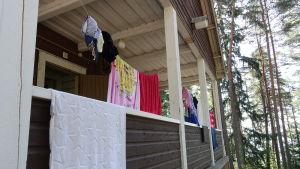 På terassen av en stuga i skogen hänger handdukar och baddräkter på tork.