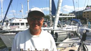 Martti kautto, en man med vit skärmmössa och vit tröja står i en gästhamn bland båtar.