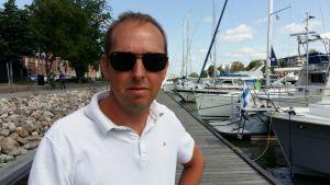 Kenneth Blomster, en man med solglasögon och vit pikéskjorta, står på en brygga med sgelebåtar.