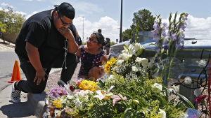 Två personer gråter vid blommor.