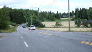 Fyra bilar kör på en asfaltsväg.