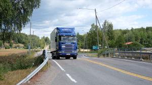 En lastbil kör på en väg vid en korsning.