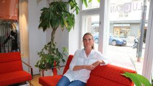 En kvinna sitter på en soffa. Hon är klädd i skjorta och jeans och bakom henne finns ett fönster som vetter mot en gata. På gatan står en bil och en motorcykel.