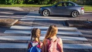 två flickor med ryggsäckar sitter vid övergångsställe.