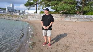 Kim Lindström står på en strand och ser ut mot havet.