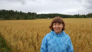 Helena Äijö står i förgrunden iklädd en blå vindjacka. Bakom henne ses sädesslag växa på en stor åker. Längst i bakgrunden skog och en grå, mulen himmel.