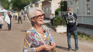 Nainen seisoo puutalojen reunustamalla tiellä hymyillen.