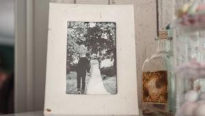 Valkoisissa kehyksissä mustavalkoinen hääkuva, jossa nainen ja mies suutelevat puiden alla.