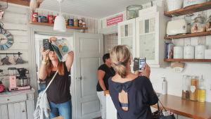 Kolme naista keittiössä, kaksi ottaa kuvia kännyköillään sisustuksesta.
