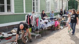 Kirpputoripöytiä, myyjiä ja ohikävelijöitä kadulla, vihreän puutalon edustalla