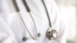 En person i läkarrock med ett stetoskop på bröstet.