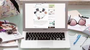 En laptop på ett stökigt skrivbord. På laptopens skärm syns en webshop.
