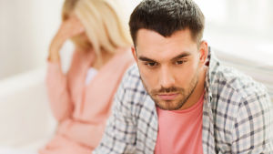 en man och en kvinna sitter på soffan och undviker varandras blickar.