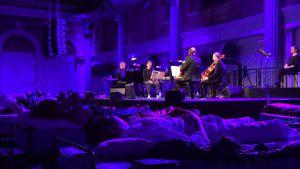 Människor ligger och sover på sängar framför en orkesterscen med en klassisk orkester.