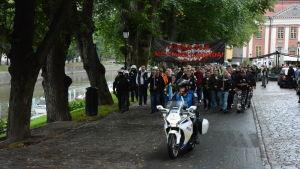 Demonstranter marscherar längs Aura å. En motorcykelpolis åker framför dem.