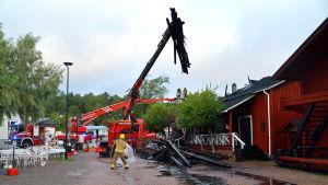 En brandbil med lyftkran lyfter trädbalkar från en röd bodas tak.