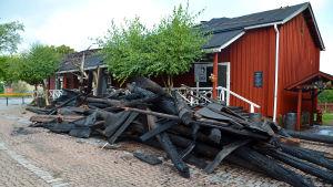 Svartbrända träbalkar utanför restaurangen.