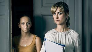 kaksi naista seisoo vakavana oven suussa, toinen on opiskelija ja toinen opettaja.