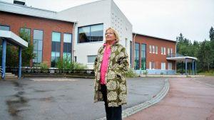 Merja Laaksonen som står på Aleksis Kiven koulus bakgård i Sjundeå.