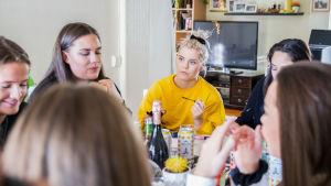 Ulrikke Falch med andra tjejer runt ett bord.