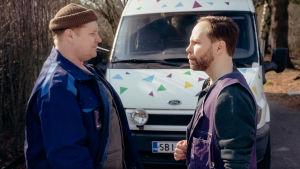 Santtu Karvosen ja Juho Milonoffin esittämät autot seisovat kasvotusten ulkona valkoisen pakettiauton edessä. Karvosella tupakka suussa.
