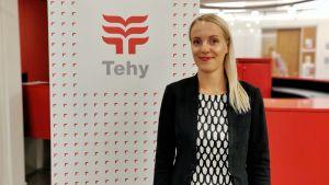 En kvinna står bredvid en Tehy skylt framför ett rött bord